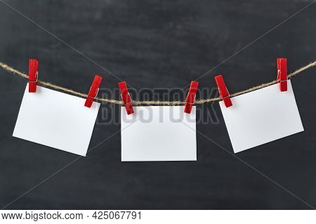 Blank Paper Cards Hang With Clothespins On Rope. Black Background. Copy Space.