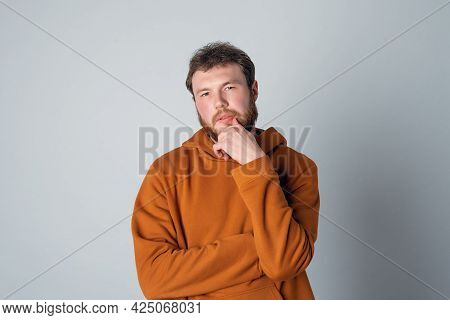 Making Up Great Idea. Thoughtful And Creative Guy With Beard And Messy Hair In Stylish Hoodie Standi