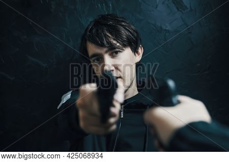 First-person View Of Hand With Gun Pointed At Guy With Pistol. Two Shooters Threaten Each Other With