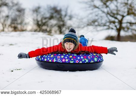 Active School Boy Sliding Down The Hill On Snow Tube. Cute Happy Child Having Fun Outdoors In Winter