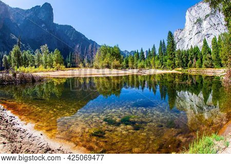 Beautiful sunny day in the park valley. Yosemite Park is located on the slopes of the Sierra Nevada. Charming El Capitan and trees is reflected in the smooth water of little lake