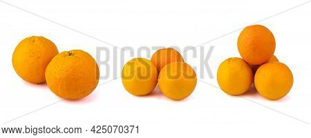 Large Oranges Are Arranged In Three Piles In Different Quantities, Isolated On A Clean White Backgro