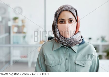 Waist Up Portrait Of Modern Middle-eastern Woman Wearing Mask And Looking At Camera While Standing I