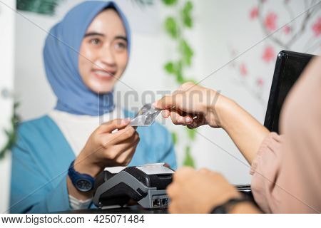 A Veiled Business Woman Smiles As She Returns Credit Cards To Customers While Paying Cashless At The