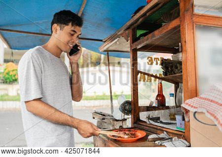 Sate Ayam Seller Cooking The Food While Talking On A Phone