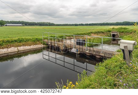 The Water Foams At The Other Site Of The Overflowing Weir In A Dutch Polder Landscape. The Small Wei