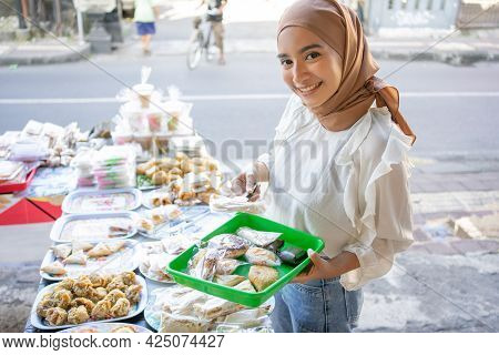 A Beautiful Girl Wearing A Headscarf Uses Tongs And Carrying A Plastic Tray Choosing Snacks
