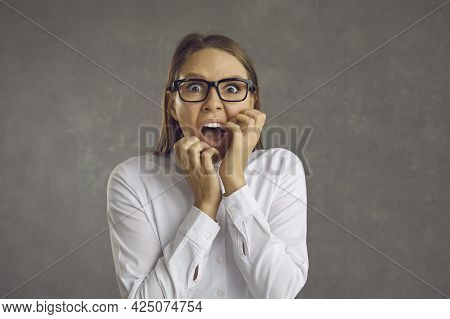 Studio Portrait Of A Scared Young Woman In Glasses Panicking And Screaming Loudly