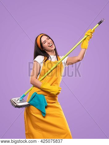 Delighted Housemaid In Apron And Gloves Prepending Playing Guitar On Brush On Purple Background In S