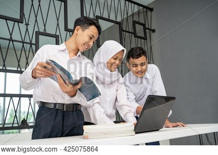 Three Asian Teenagers Study Together In School Uniforms Using A Laptop And Several Books