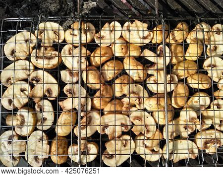 Tasty Delicious Champignons Are Cooked On Coals. Grilled Mushrooms Roasting On Bbq Grill Outdoor. Gr