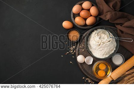 Ingredients For Cooking Flour Dishes. Flour, Eggs, Sugar On A Black Background. Top View, Copy Space