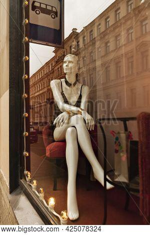 White Plastic Mannikin Figure Of Woman In Black Top Sits In Showcase Shop Window Under Bus Stop Sign