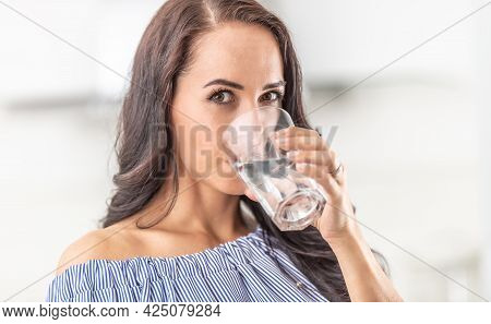 Woman Rehydrates By Drinking From A Big Glass Of Water.
