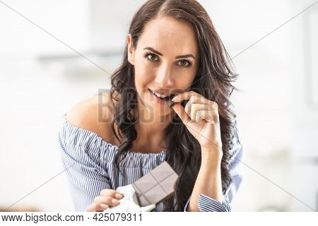 Brunette Nibbles On A Chocolate Bar Indoors, Looking At The Camera.