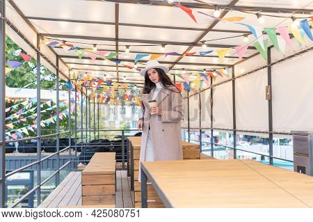 Portrait Of A Beautiful Woman With A Cup Of Coffee On The Veranda In A Cafe