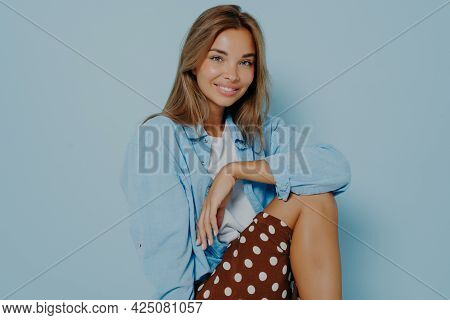 Studio Portrait Of Beautiful Young Brunette Woman, Sitting Over Blue Background, Posing At Camera An