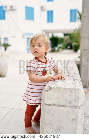 Little Girl Stands Near A Stone Fence In The Courtyard Of The House