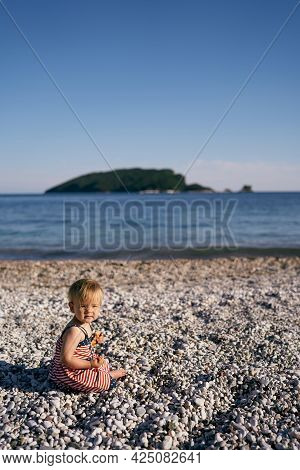 Little Girl Sits On A Pebble Beach And Holds A Pancake In Her Hand