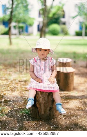 Little Girl In A Hat Sits On A Tree Stump In The Yard