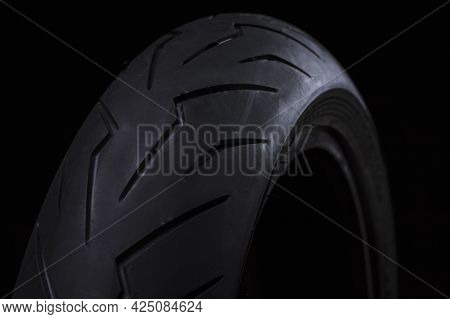 Closeup Image Of New Racing Road Motorcycle Tyre Against Black Background