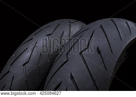 Closeup Image Of Set Of New Racing Road Motorcycle Tyres Against Black Background