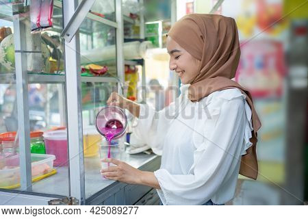 Ice-seller Hijab Girl Holding A Blender While Pouring Fruit Juice Into A Plastic Cup