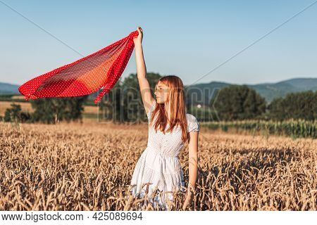 Outdoors Photo Of Young, Ginger Girl In White Dress Holding A Red Scarf Fluttering Up In The Air. Co