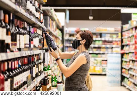 Asian Woman In Protective Mask Choosing Wine In A Wine Shop