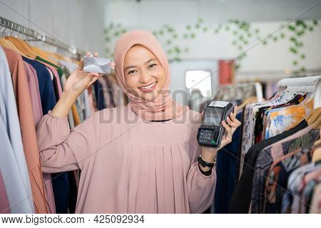 A Veiled Business Woman Holding A Credit Card And An Electronic Data Capture Machine