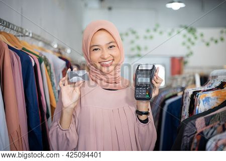 Smiling A Veiled Woman Holding A Credit Card And An Electronic Data Capture Machine
