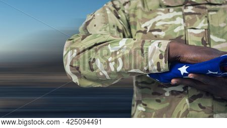 Composition of midsection of soldier with hand on folded american flag. patriotism, independence and honour concept digitally generated image.
