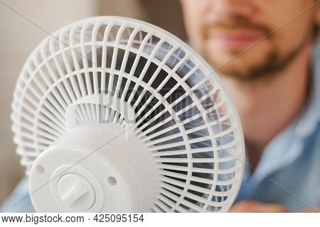 Man Enjoying Air Flow From Fan In Office. Businessman Refreshing In Front Of Air Electric Ventilator