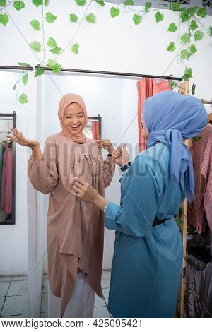 Beautiful Girl In A Veil Trying On Clothes In A Changing Room In Front Of The Mirror So That Her Fri