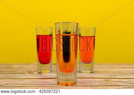 Colorful Drinks On Wooden Table. Small Glass Glasses With Colorful Drinks On Wooden Table With Yello