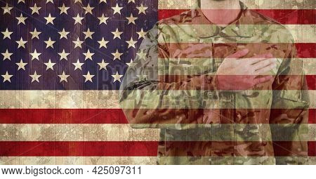 Composition of midsection of male soldier with hand on heart, against american flag. patriotism, independence and military concept digitally generated image.