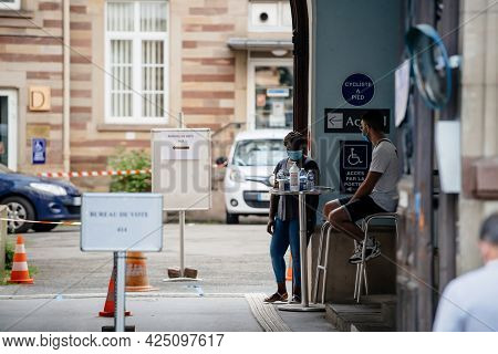 Strasbourg, France - Jun 27, 2021: Workers With Masks And Alcohol Sanitizer Gel At French Polling St