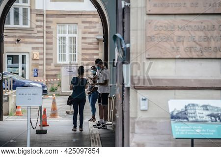 Strasbourg, France - Jun 27, 2021: Workers With Masks Serving Alcohol Sanitizer Gel For Voter At Fre