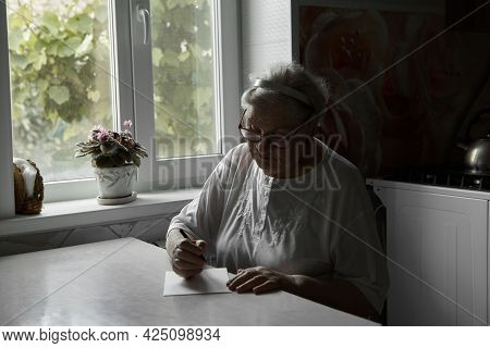An Elderly Woman Writes At Home On A Piece Of Paper. Hobbies Of Pensioners. Remote Communication, Se