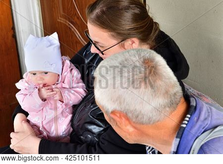 A Young Mother With A Newborn In Her Arms Is Enjoying Together With Her Old Father