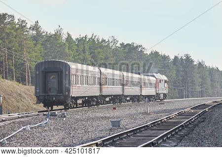 The Soft Focus Of A Red-gray Train And Railway Against A Background Of Green Forest And Blue Sky. Th