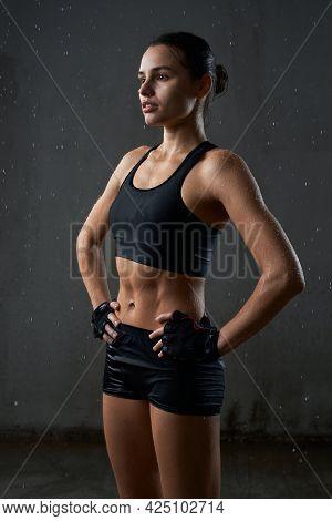 Portrait Of Wet Fit Caucasian Female Model Holding Hands On Waist, Wearing Black Sportswear Standing