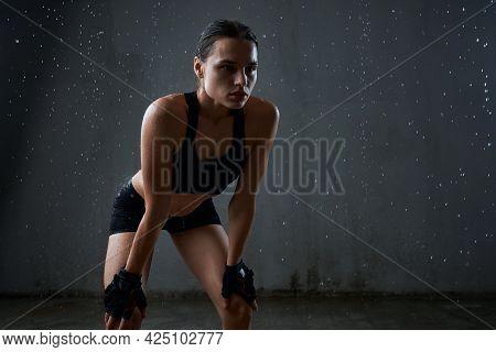 Portrait Of Wet Fit Female Model Holding Hands On Knees, Wearing Black Sportswear Having Rest After