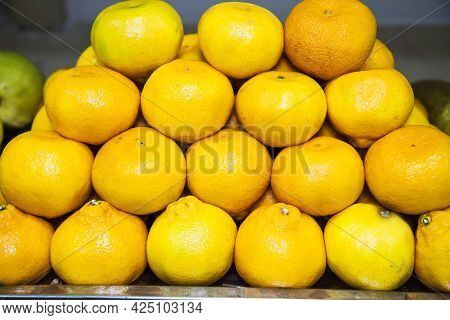 The Fruits Of Mandarin (latin Cītrus Reticulāta) Are Yellow In Color, Folded Into A Pyramid. Fruits