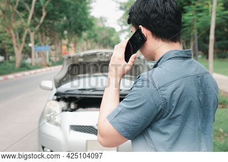 Asian Man Using Mobile Phone Calling For Assistance After A Car Breakdown On Street. Concept Of Vehi