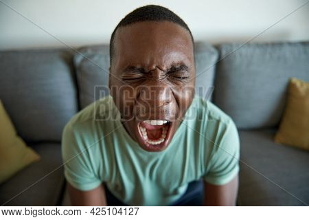 Young African Man Screaming In Anguish At Home