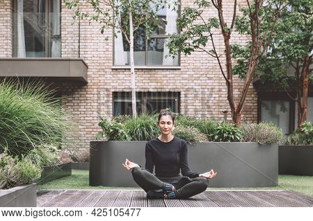 Beautiful Slim Young Woman Is Doing Online Yoga At The Landscaped Inner Garden And Is Sitting In Eas