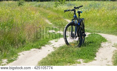 Bike Stands On The Road In The Field. A Mountain Bike Stands On A Field Path With Green Grass. Mount