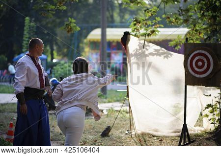 Girl Throws Knives At A Wooded Target. Woman With Red Hair Throwing Knife At Bullseye Target With A