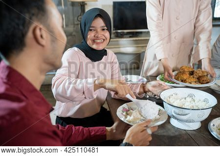 A Girl In A Black Headscarf Serves Rice To Her Boyfriend At Lunch While Hanging Out